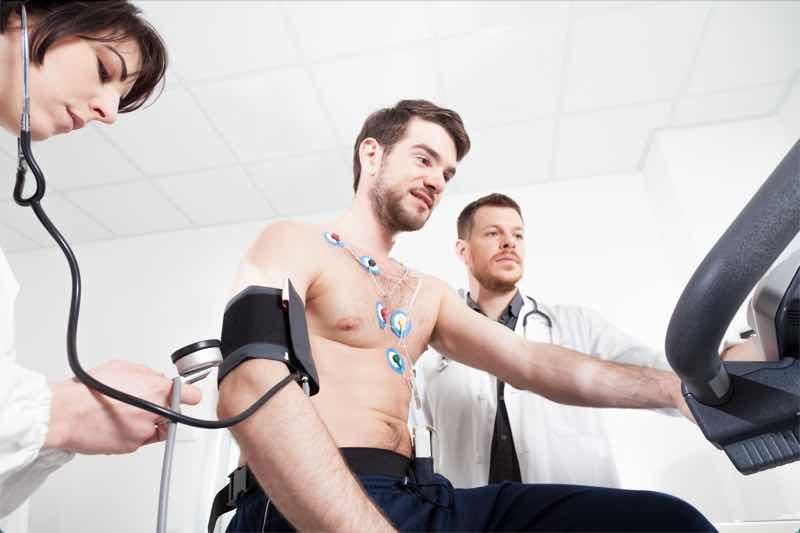 Das Bild zeigt einen Mann beim EKG auf einem Ergometer